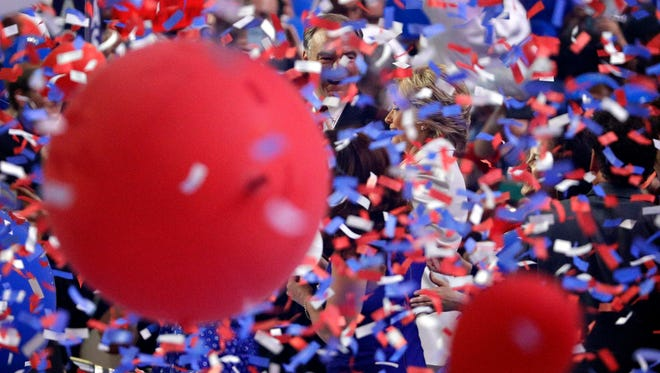 Democratic presidential nominee Hillary Clinton, right, and vice presidential nominee Sen. Tim Kaine, D-Va., react as balloons and confetti fall during the final day of the Democratic National Convention, Thursday, July 28, 2016, in Philadelphia.