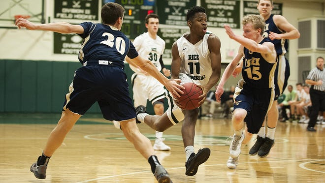 Rice's Ben Shungu (11) drives to the hoop between Essex's Peter Barrow (15) and T.J. Reed (20) during a game between the Essex Hornets and the Rice Green Knights Tuesday night.