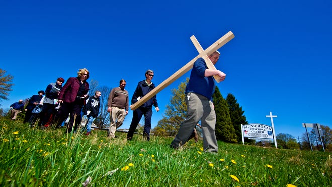 Parishioners from three churches , St. Nicholas Episcopal, St. Andrews Presbyterian and Kingswood United Methodist participate in a processional with Clergy and congregation carrying a cross down Del. 4 in Newark. in honor of Good Friday in 2012.