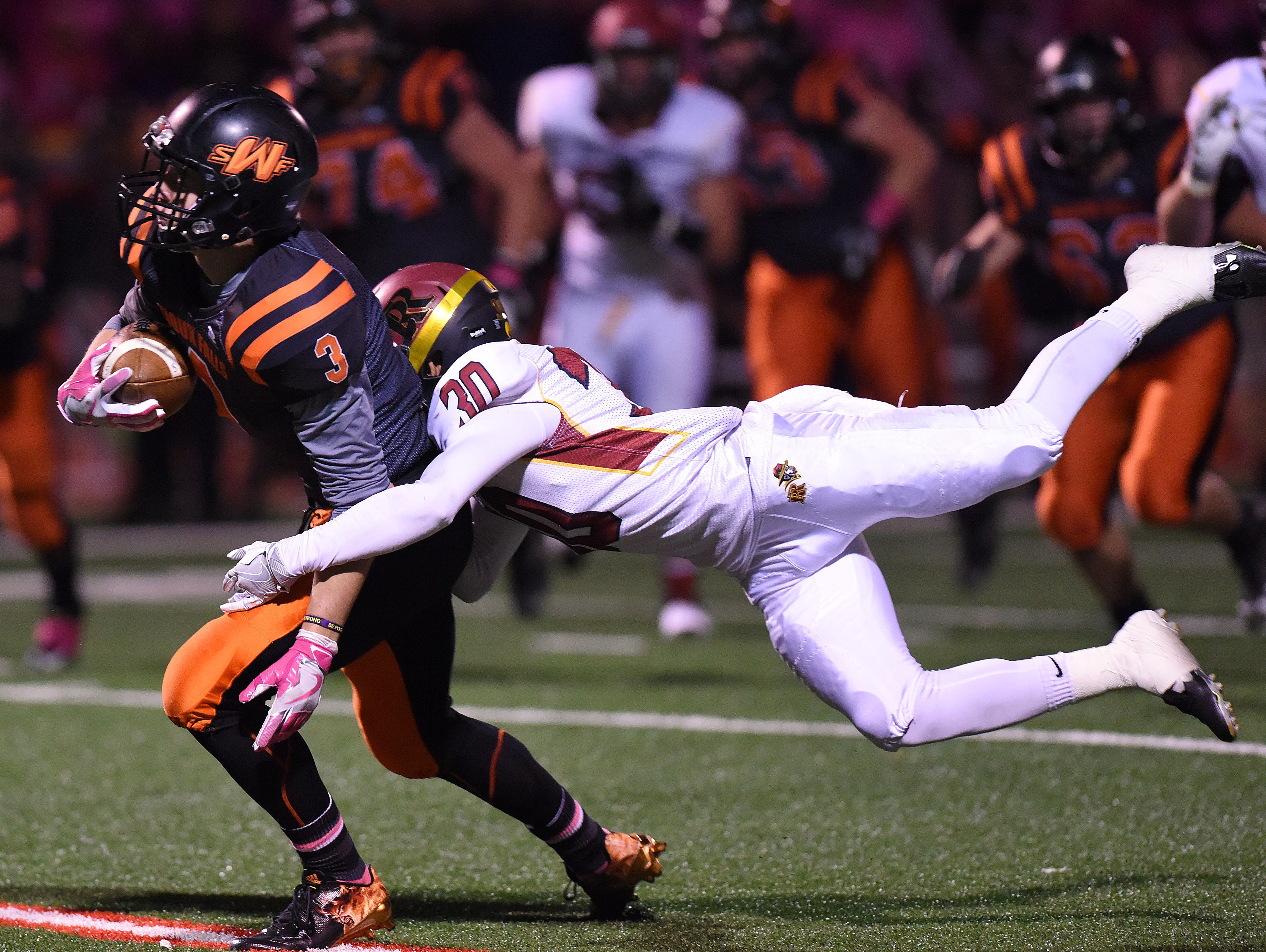 Washington's Logan Uttecht is tackled by Roosevelt's Dylan Garrow on Thursday at Howard Wood Field.