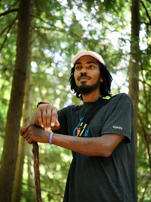 """Daniel White, also known by his trail name, the """"Blackalachian,"""" leads a walk through the botanical garden at UNC Asheville July 12, 2018."""