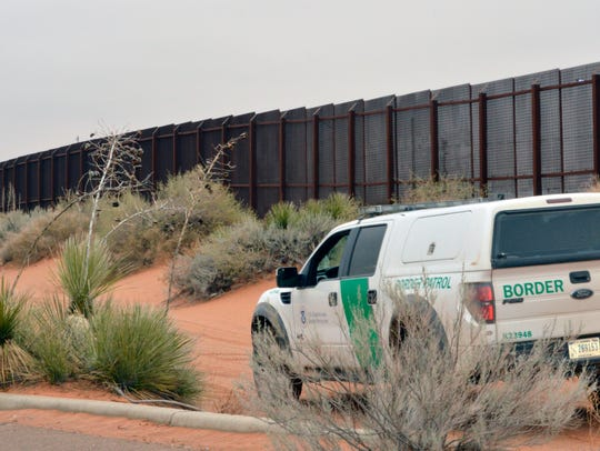 A U.S. Border Patrol vehicle drives next to a U.S-Mexico