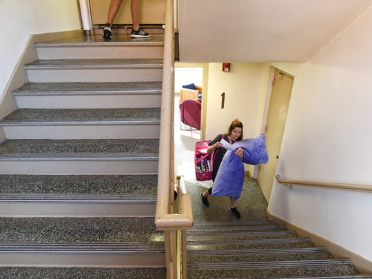 Carmie Shook climbs the stairs in Memorial Hall on the Muskingum University campus in New Concord during move in day on Friday.