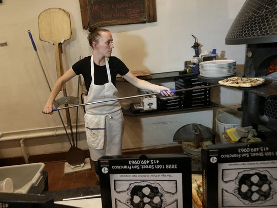 Sabrina Ferguson takes a pizza from the oven at Mozzeria in San Francisco. Mozzeria owners Russ and Melody Stein as well as staff workers are deaf.