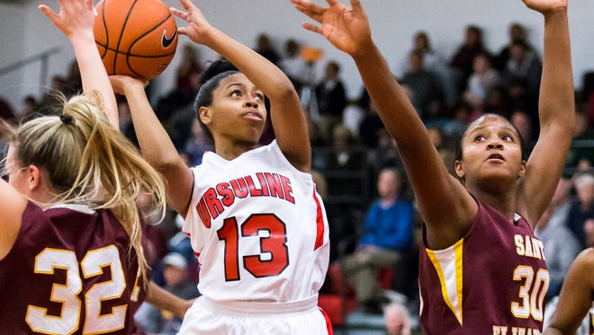 Sabriya Harris (13) of No. 1 Ursuline shoots between Alexis Bromwell (32) and Alanna Speaks (30) of No. 4 St. Elizabeth during the Raiders' 60-38 win on Jan. 5. The Catholic Conference rivals meet again at 7:30 p.m. Tuesday at St. Elizabeth.