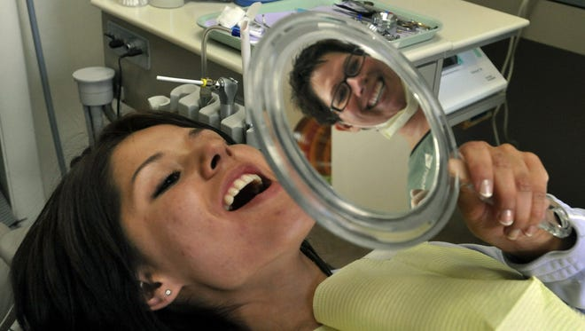 In this Coloradoan library photo, Louisa Caraveo of Fort Collins takes a peek at her new filling as dental assistant Diane Snell looks on during a free dental day at Foothills Family Dentistry, 523 Remington St. Friday June 24, 2011.