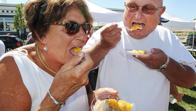 Walter & Monica Tomczyk from Rehoboth Beach sample peach pie as the Milton Farmers Market held their Annual Peach Festival at Dogfish Head Brewery in Milton on Friday July 25, 2015.