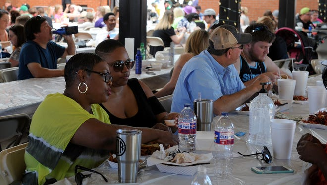 Attendees dig into their plates of crayfish at the 10th annual Cajun Fest Saturday, May 13, 2017, in the Downtown Farmer's Market at Eighth and Ohio. Proceeds from the event are split between the Downtown Wichita Falls Development Inc. programs and the Elks Lodge #1105 charity fund.
