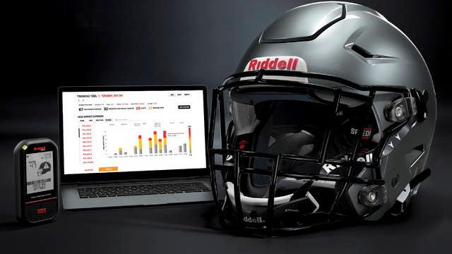 In this May 2020 photo provided by Riddell, a Riddell SpeedFlex helmet sits next to a computer screen displaying information from the InSite tool. Teaming with Catapult, an Australia-based technology company, Riddell is providing coaches, players and medical staff detailed information regarding anything from practice regimens to helmet contacts to overall preparation for athletes.