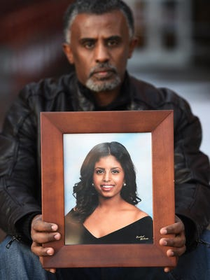 Fanuel Gebreyes, father of Aden Hailu, holds a portrait of his daughter near an entrance to Argenta Hall on the University of Nevada campus in Reno on Jan. 9, 2016. Hailu lived in Argenta Hall while a student at the university.