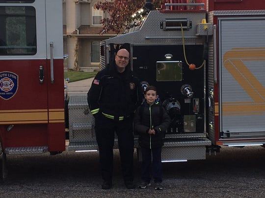 Nolan Falson won a coloring contest and first prize was a ride to school on a fire engine. With him is South Lyon Fire Lt. Jeff Noechel.