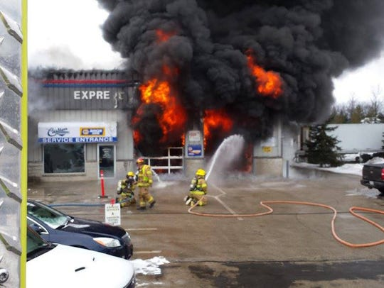 Firefighters work the fire at Carlton Automotive Saturday