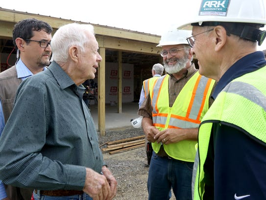 Carter talks with a construction worker after touring