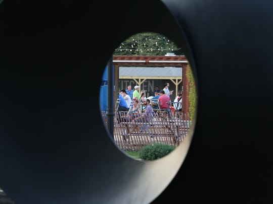 Patrons at the Constitution Yards beer garden are framed by a sculpture on the Wilmington Riverfront.