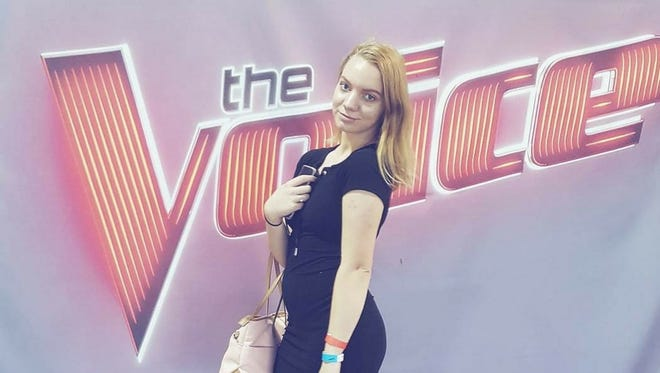 Catilyn Boyd, 16, takes a photo in front of The Voice logo at her second audition in Houston, Texas. Boyd will be featured on Season 14 of the NBC show.