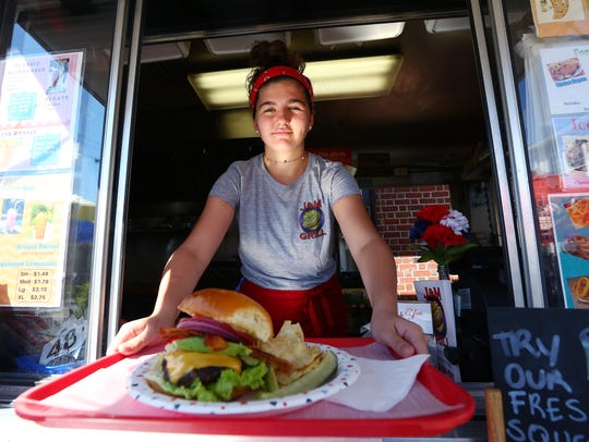 Gina Lombardo with a cheeseburger at J&M Grill, a large