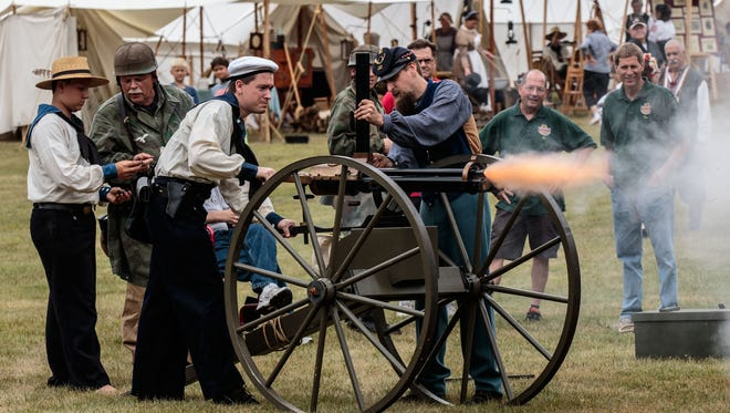 Re-enactor Andrew LaRoche (center) of Waukesha spins a crank to fire (blanks) through a Civil War gatling gun as Michael Marsh of Neenah (right) feeds the ammunition during 2015 Heritage Weekend in Lisbon Community Park.
