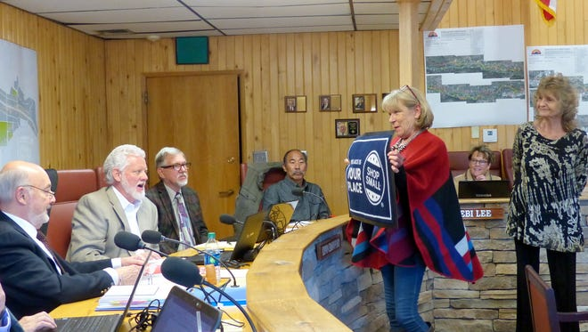 "While Teri Sodd, president of the Midtown Merchants, watches, Ruidoso Valley Chamber of Commerce Executive Director Becky Brooks presents to village councilors a welcome mat reminding people to ""shop small"" and patronize local businesses."