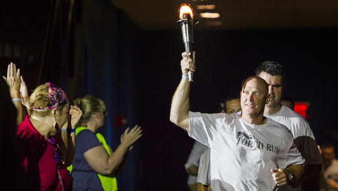 Christopher Popp runs the torch into the arena during the Opening Ceremonies of 2015 Special Olympics Delaware competitions at the Bob Carpenter Center in Newark on Friday afternoon.