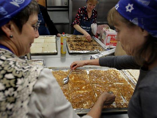 Penny Yood, left, and Elaine Cooper prepare Matzah
