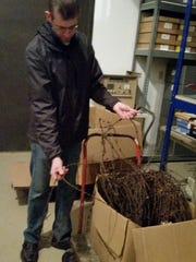 """Adam Smith shows a large wire donation from Robert """"Bob"""" Diederich in the Stearns History Museum shed in Heritage Park."""