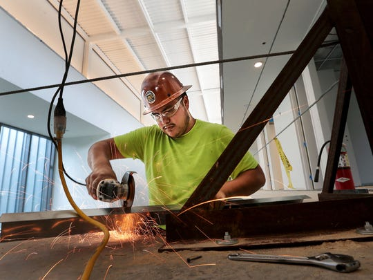 Luis Barajas grinds metal for hand rails at the new Ballet Memphis headquarters which is under construction at the corner of Madison and Cooper in Overton Square.