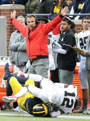 Ohio State coach Urban Meyer signals after a pass play during the Buckeyes' 31-20 win over Michigan on Saturday, Nov. 25, 2017 at Michigan Stadium.