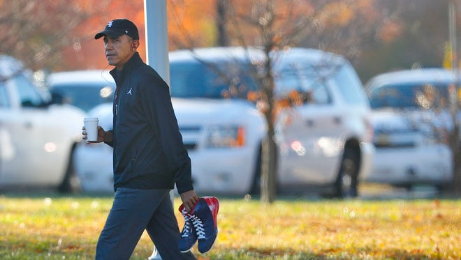 President Obama carries a pair of sneakers as he arrives for a private game of basketball at Fort McNair on Nov. 8, 2016.