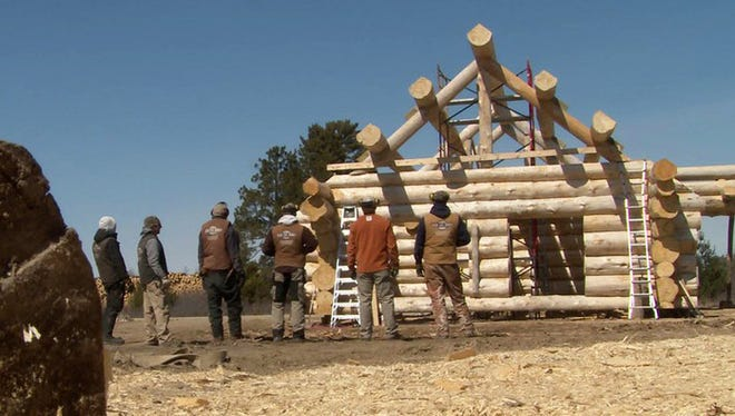 "Crew admires a cabin shell on ""Cabin Fever."""