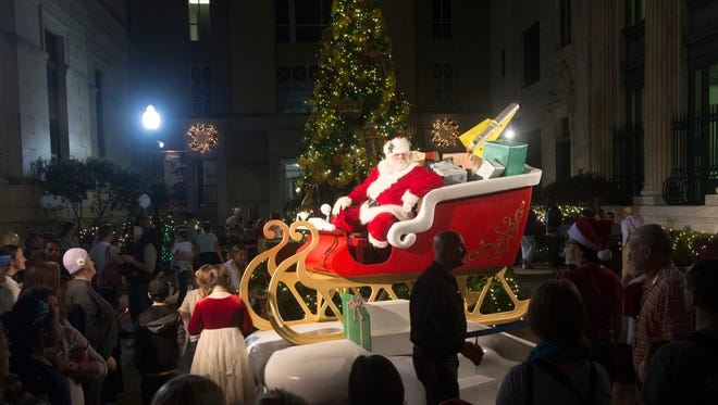 A large crowd gathers around Santa Clause outside the Artel Gallery to get a good look at the top Elf at the end of Friday night's Elf Parade. The annual event marks the kickoff to Winterfest and the lightning of the Christmas lights along Palafox Street.