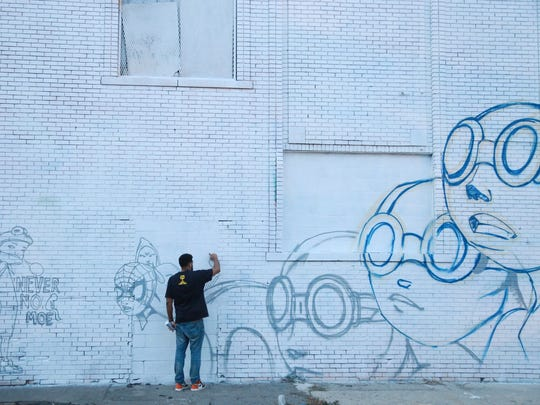 Artist Hebru Brantley works on a mural during the Murals in the Market festival on Friday September 18, 2015 at the Eastern Market in Detroit. About 40 artists are on hand creating street art through the week.