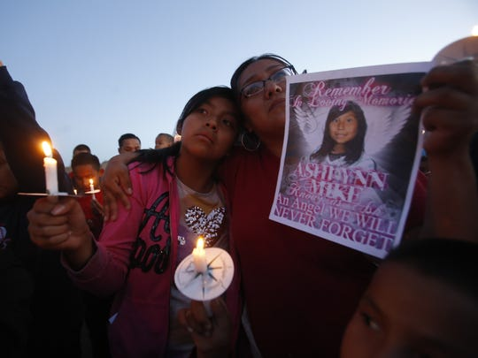 From left, Klandre Willie and her mother, Jaycelyn Blackie, of Aztec, participate in a candlelight vigil on Tuesday for Ashlynne Mike at the San Juan Chapter house in Lower Fruitland.