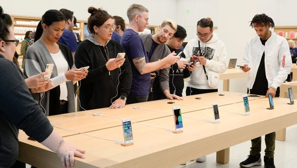 Customers tryout display iPhones as they wait their