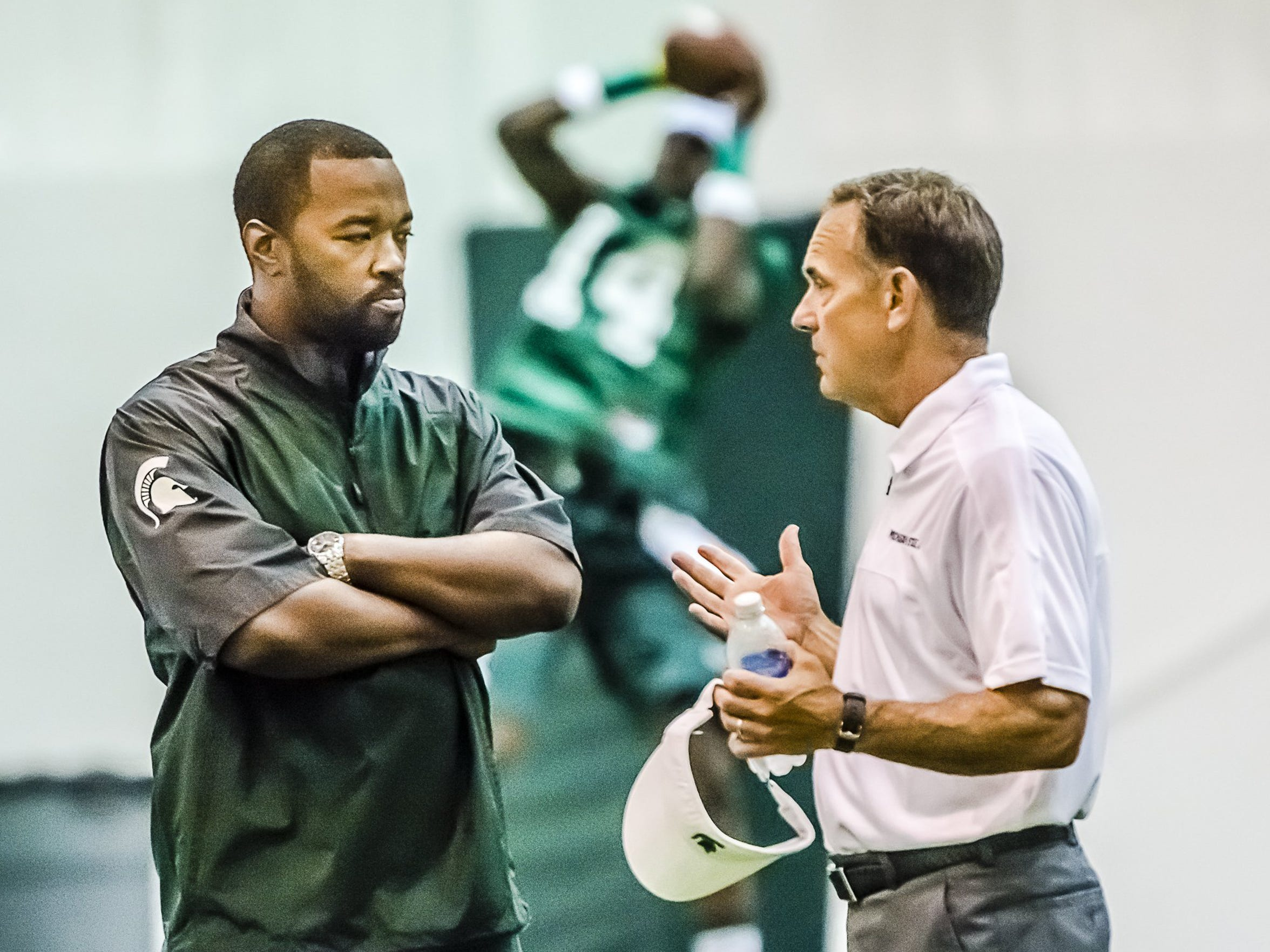 Coach Mark Dantonio, right, speaks with Curtis Blackwell, the new MSU director of college advancement and performance/camp director.