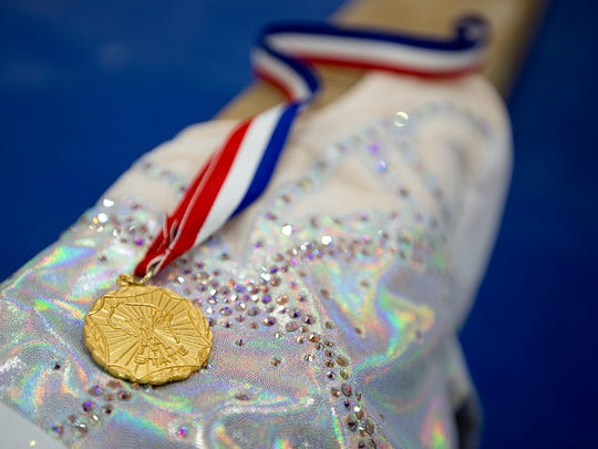 Sophomore Tia Dorshorst's  state championship medal that she won last year competing in the beam is displayed on top of the leotard that she wore during the state championships at Lincoln High School in Wisconsin Rapids, Wednesday, Dec. 16, 2015.