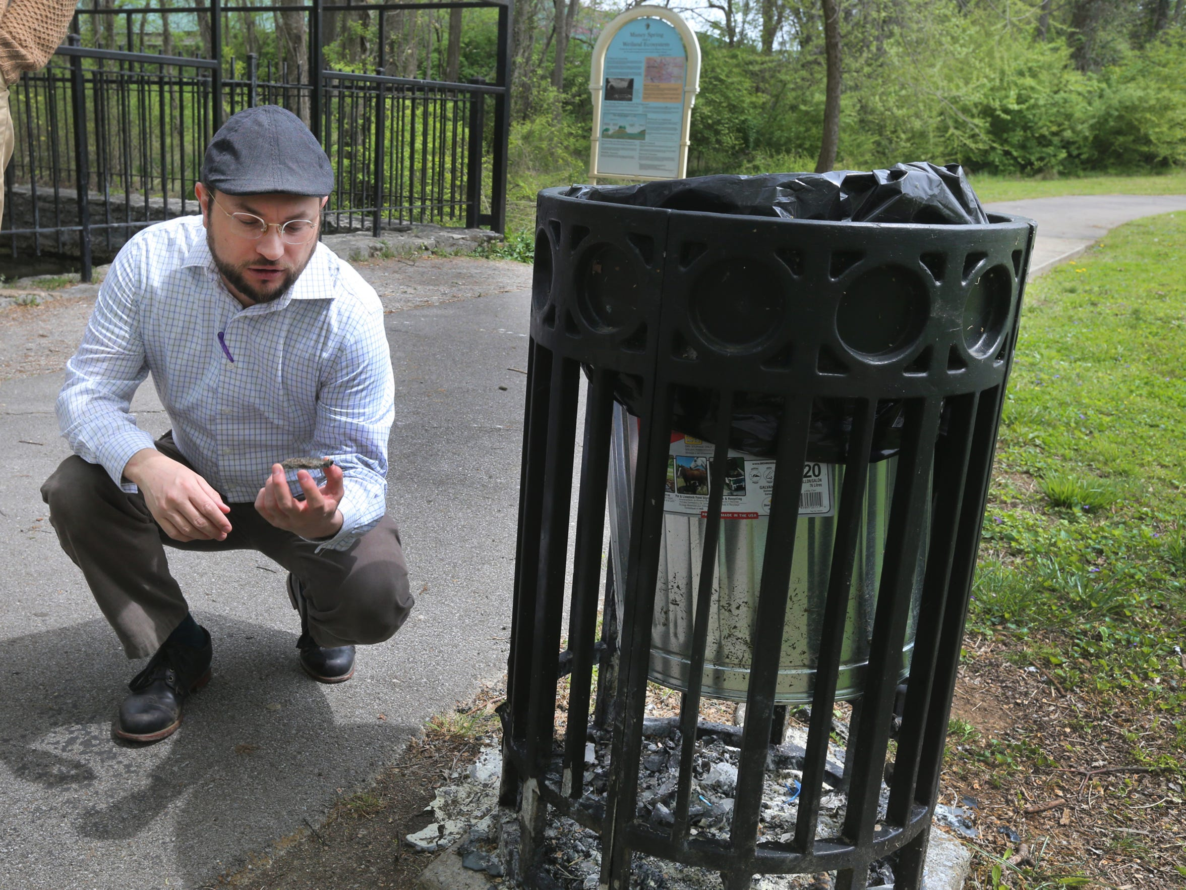 James Manning shows off a burned trash can that no longer has a cap at Oaklands Park during a walk around the area on Wednesday, April 13, 2016.