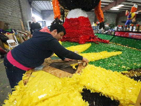 Stephanie Weber works on a float for the Olympian Fitness Center in a warehouse in Southeast El Paso Tuesday.