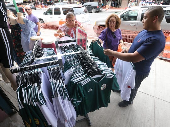 Salesman Emmanuel Burciaga, right helps shoppers find the correct size of shirt sporting the Mexican soccer team loco at a rack outside Andrea's clothing store at 625 South El Paso Street Friday.