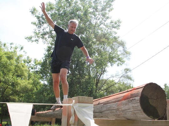 Mike Slusser of Novi attempts to cross the second half of the first obstacle on the Forge Through Hell 5K course on Saturday. Contestants here had to cross a 20-foot-long pole as it rolled back and forth between two supports. For Slusser, the obstacle proved unforgiving.