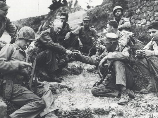 Ernie Pyle takes a break with some Marines on Iwo Jima in 1945.