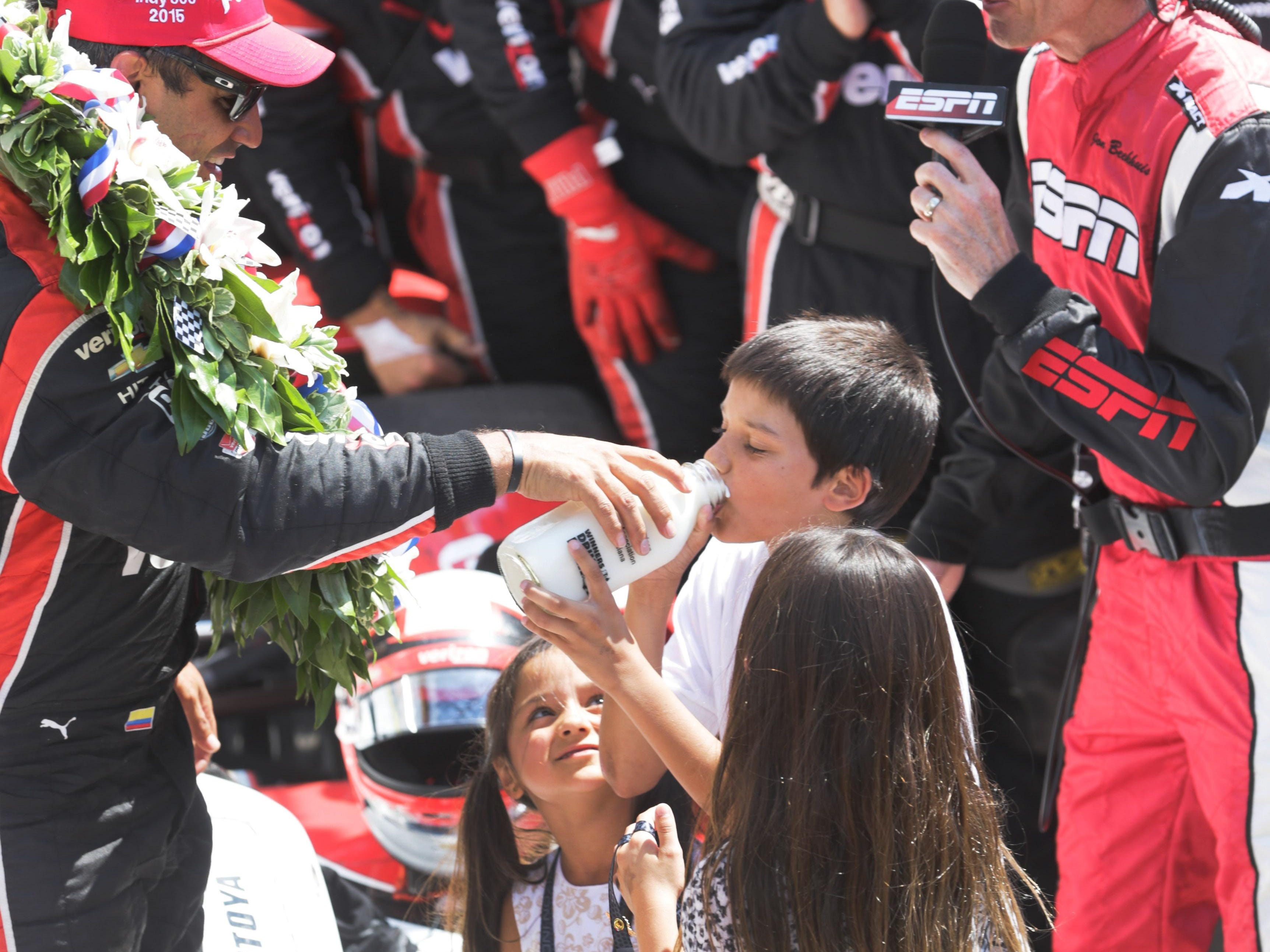 Juan Montoya in Victory Circle gives son Sebastian a drink of the milk after winning the 99th running of the Indianapolis 500 as daughters Manuela and Paulina look on. May 24, 2015