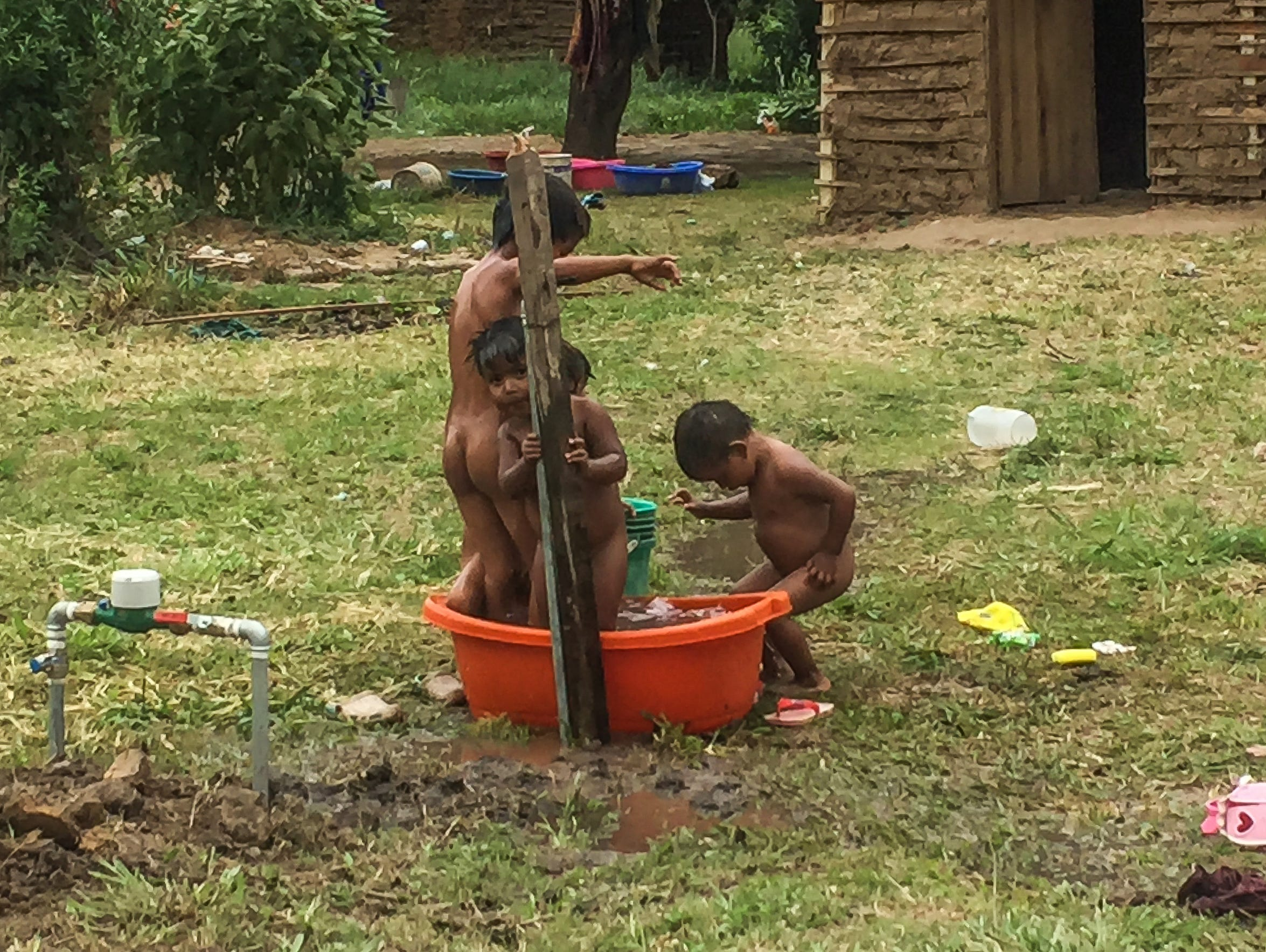 Children wash beneath a water spigot in an Ayoreo village