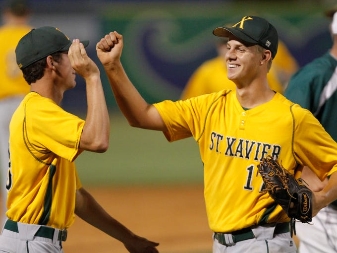 St. Xavier's Joshua Finerty, right, is congratulated by Grant Wessling after defeating North Bullitt 13-4 in their semifinal game in the KHSAA State Baseball tournament in Lexington.  June 6, 2014