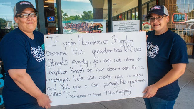 Jennifer Ayala and her sister Melissa Cruz, right, hold the original sign on their door telling anyone who is homeless or struggling to come in and ask for help and a free meal and they will give it to them at Slack's Hoagie Shack in Falls.