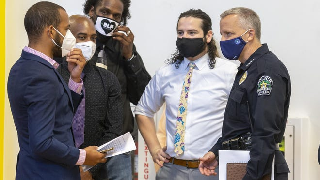 From left, Eric Brown, Ahmed Toure, Michael Burnett and Alexander Blum of the community group Just America speak with Austin Police Chief Brian Manley before a news conference Thursday.