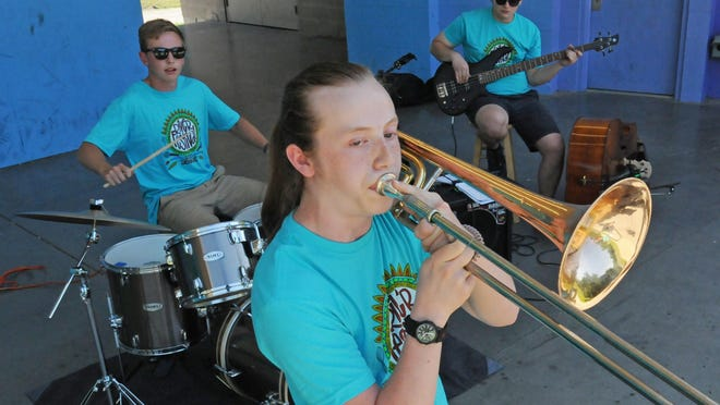 "Former and current Salina Central Jazz Ensemble students Miles Denning, plays the drums, as Tyler Corl belts out a trombone solo, with Nelson Gutsch playing the bass guitar while performing jazz music on the Eric Stein Stage at Oakdale Park on Friday. The jazz ensemble ""Paper Mache"" was scheduled to play in the 2020 Smoky Hill River Festival that was canceled due to the coronavirus and the band memebers decided to play even without the festival."