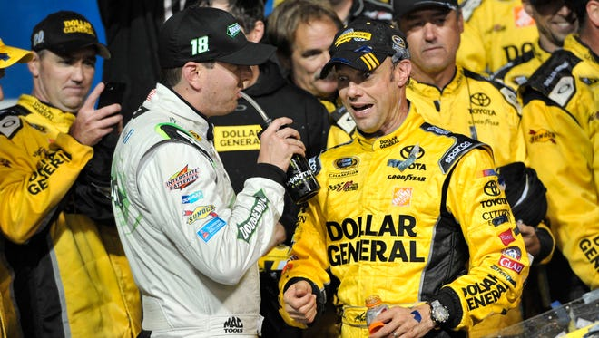 Sprint Cup Series driver Matt Kenseth (right) celebrates in victory lane with teammate Kyle Busch (left) after winning the Geico 400 at Chicagoland Speedway on Sept. 15.