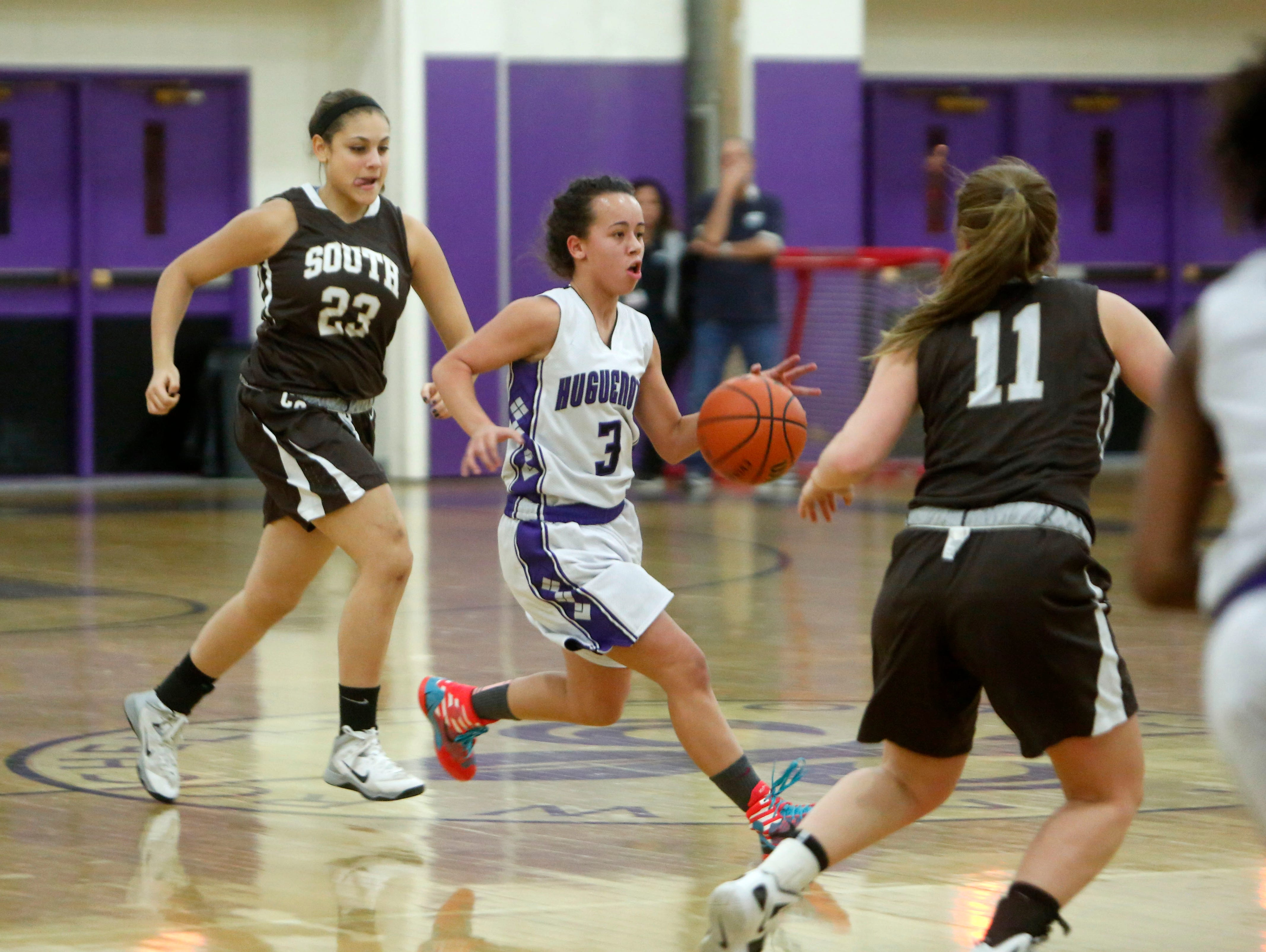 New Rochelle's Kayla Correa in action against Clarkstown South's Britney Gallagher, left, and Kayla Tucek during a girls basketball game, Dec. 10, 2014 in New Rochelle. New Rochelle won, 63-60.