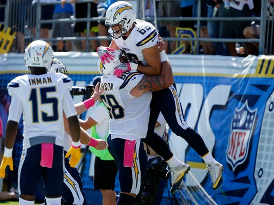 San Diego Chargers tight end Hunter Henry, top, is lifted by teammate Matt Slauson after scoring a touchdown during the first half of an NFL football game against the New Orleans Saints, Sunday, Oct. 2, 2016, in San Diego. (AP Photo/Lenny Ignelzi)