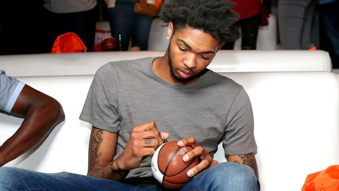Former Duke University basketball player Brandon Ingram signs a miniature basketball during an event leading up to the NBA draft Thursday.